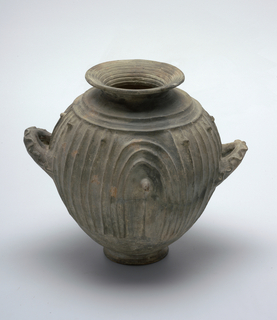 Bulbous, inverted ovoid form of grey-black volcanic clay; flaring circular mouth, two loop handles, small circular foot; the body and hadles with raised curvilinear and fluted  decoration.