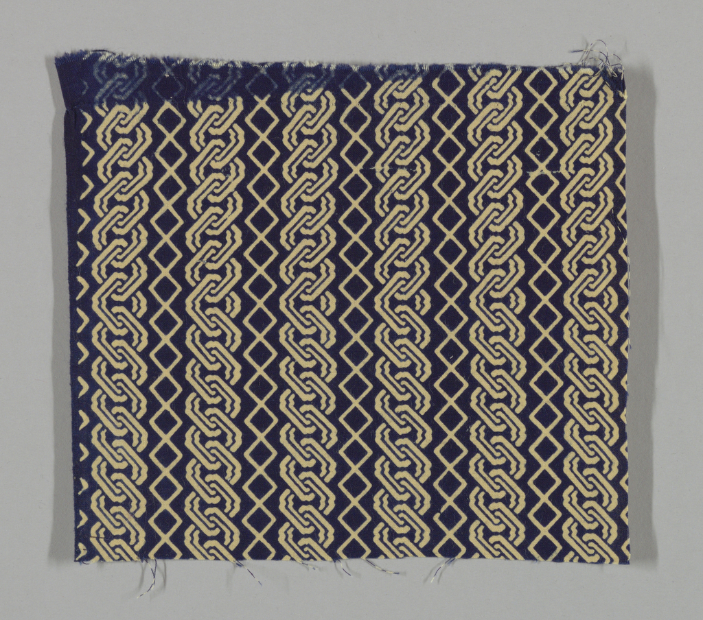 Pattern of linked shapes, like chain, in pale yellow on dark blue ground. Double faced.