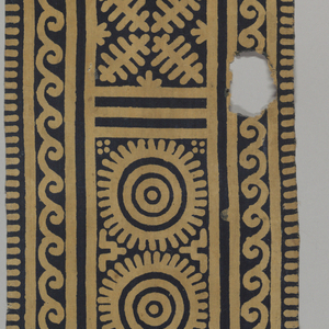 """Long narrow strip of cotton forming a sash, turban, or hanging. Patterned with repeats of geometric shapes (including """"tumpal"""" motif at ends) arranged symmetrically--the center line being in the middle of the length--but the halves are not exactly identical. Tan pattern on a dark blue ground."""