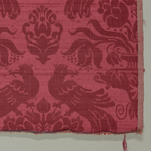Sample of red satin in a pattern of large-scale vases of flowers with confronted peacocks holding sprigs in their beaks. Designed and manufactured in the style of seventeenth-century Sicilian damask.