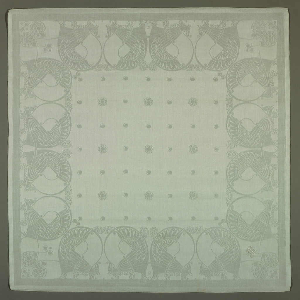 Square linen damask napkin with a field of regularly spaced floral dots and a deep border of stylized cocks pecking at seeds.