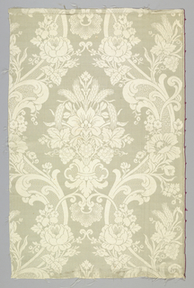White damask with a pattern of symmetrically swinging broad bands with flowers and foliage enclosing central symmetrical group of flowers, grapes and wheat.