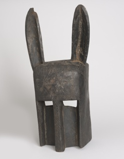 Hollowed rectangular anthropomorphic form with long tapering ears framing deep bulbous forehead above pierced rectangular eyes, and bisected by elongated straight nose. Dark brown patina.