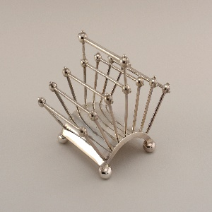Electroplated silver. Curved base, four bun feet.  Seven sets of parallel posts with connecting rods and ball joints, the center ones with an extra raised section to serve as a handle.