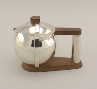 Globular body with flush-fitting domed cover.  Raised square band encircles body at right angle to handle, with shape continued on cover.  Triangular spout with lozenge-shaped opening.  Tubular handle attached to body with walnut strut at top, and to shaped plinth that continues as base of teapot body.  Shaped wooden finial.  Cover with fitted flange closure.  En suite with 2a,b, 3a,b, 4