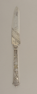 Fish knife engraved on both handle and blade. On blade: abstract and floral pattern; handle decorated with dragonflies and a character in a circle; crown-like terminal on handle.