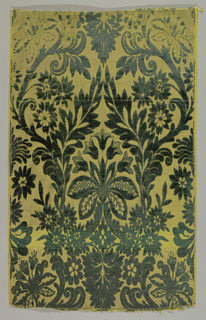 Five pieces of velvet forming a panel. Elaborate floral groups with leaves and vines in dark green velvet on a yellow and gold background. On face, extra weft floats of yellow silk alternating with metal strips.