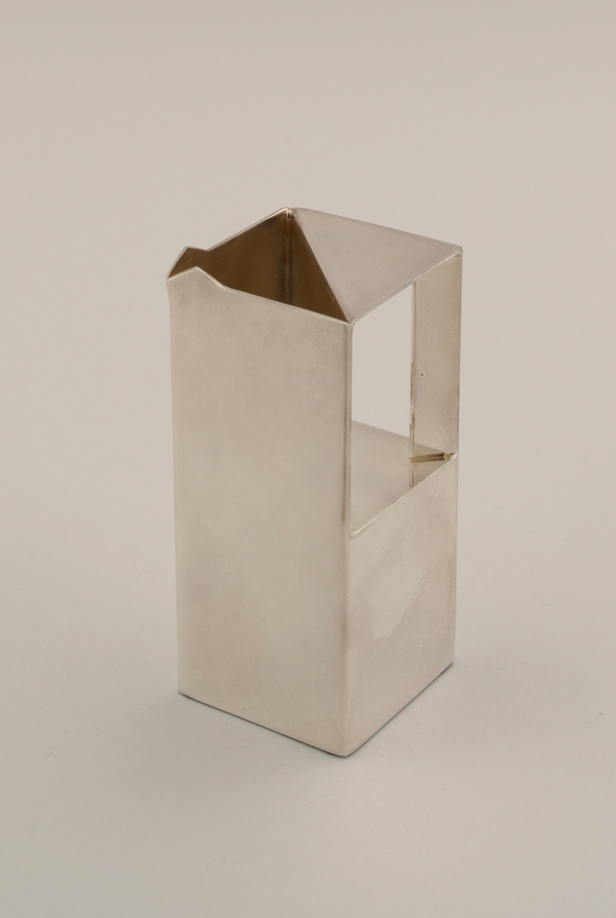 Creamer in a geometric style.  Part of a six piece tea service.  The tea service relies onpure geometric form and highly reflective surfaces for its effect.