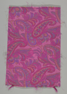 Brilliant pink material, double cloth, warp printed in large scale pattern derived from an Indian shawl design, in strong greens, red, and purple. The reverse is a strong magenta, with small-scale pattern, part of larger design on face, appearing in reverse colors on face.