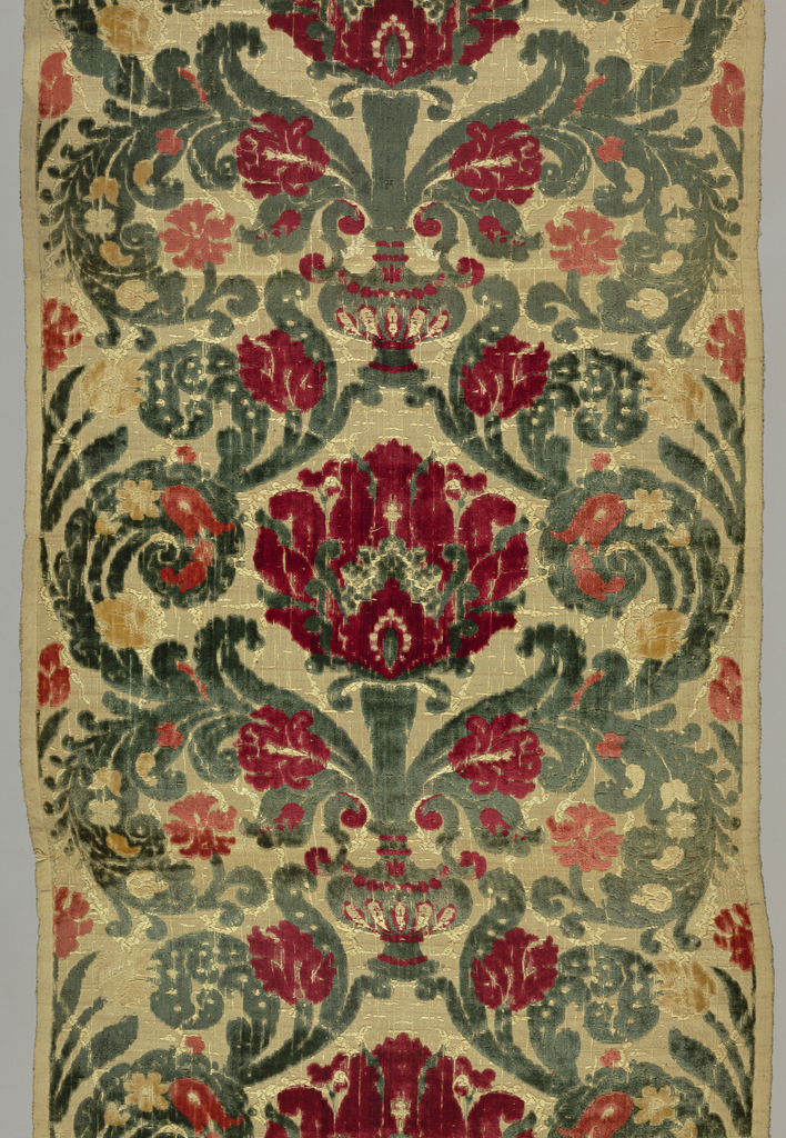 Vertically symmetrical pattern with small vase and large central flower, with subsidiary flowers and leafy scrolls in shades of red and green on an ivory ground.