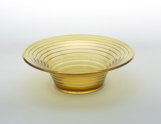 Transparent yellow body; circular everted rim, the ribbed and curved body tapering to circular base.