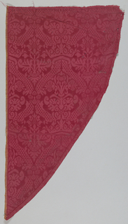 Red damask with an ogee lattice formed by a decorated vine with small triangles enclosing two types of flowering plants; the blossom in the major ogee resembling lilies. Crowns encircle the points of the two major shapes from end to end, and four lobed rosettes join the major shapes side to side.