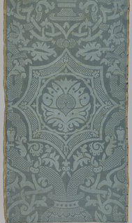 Gray-blue damask with large symmetrical design of a vase with two heavy stems framing a curved octagon with a stylized palmette inside. Highly stylized vine and leaf pattern with elaborate interlacing. Vase, vine and branches filled with a diaper pattern. Broad satin selvages striped in salmon and yellow.