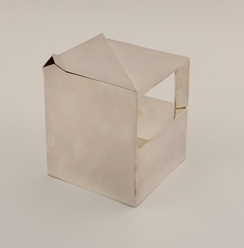 Teapot in a geometric style.  Part of a six piece silverplated tea service.  The tea service relies on pure geometric form and highly reflective surfaces for its effect.