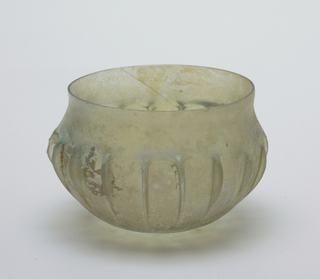 Rounded body of greenish glass with iridescence. Vessel has contracting concave neck, continued in eighteen vertical ribs at the center of the vessel's body.  Design shows derivation of Lotus-petal design.