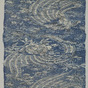 Length of resist-dyed cotton with broad sweeping water forms framing two turtles swimming toward each other, with flowering plum and pine branches. In white, gray and black on a blue ground.