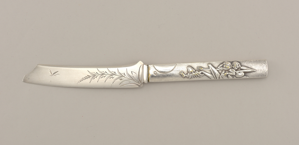 Knife in the form of a Japanese sword; handle with mottled surface, one side decorated with scene of full moon above two naked men, an octopus attacking one's leg; other side with galloping horse and phoenix in full plumage. Flat, curved blade engraved with stylized foliate decoration.