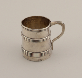 Straight-sided mug with three bands of reeding; handle possibly later addition. Monogram J. E B later.