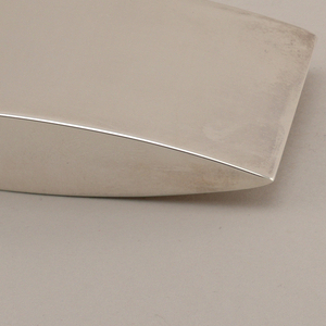 Caster with curved top and base, elongated body with pointed ends. On one side at top there are nine holes.