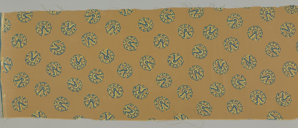 Brown ground with a design of Aztec circular motifs (Xipé emblem) in blue and yellow.