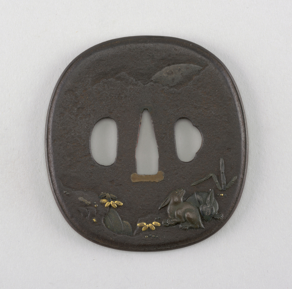 The iron tsuba is an irregular oval in shape and has a raised, rim-chased mimi (edge).  At bottom, a high relief decoration of rabbits and plants with brass details. At top,a low relief of clouds and a mountaintop, with textured tsushime hammer work.  At the center is the nakago-ana, an opening through which the sword passes. At the bottom of the opening has sekigane (plugs added to fit the tsuba to a sword) made of shakudo (a soft copper and gold alloy). On either side are ryo-hitsu, openings for the kozuka (utility knife) and the kogai (skewer tool). At left is sashi ura, the side which faces the blade, whose opening takes the hangetsu-kei (half moon) shape. Opposite is the more elaborately decorated sashi omote side, which would face the sword hilt. Its tri-lobed opening is of the suhama type, symbolically representing the coastline of Horai, the holy island of the Immortals.
