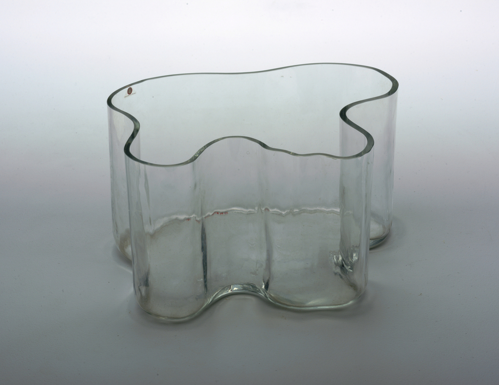 Tall, irregularly shaped clear glass vase with flat bottom; thickness of wall uiform throughout.