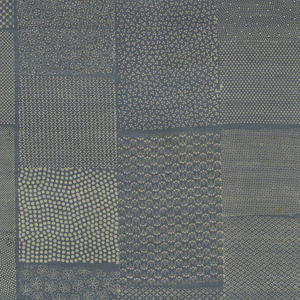 Roll composed of six sections of silk sewed end to end; one end pasted to paper on wooden roll, other pasted to paper serving as cover and bearing inscription.  Silk printed with 105 small-scale repeating patterns, largely in dot and lozenge designs, in white on a blue ground.  Patterns are in rectangles of various widths, arranged in five lengthwise bands.