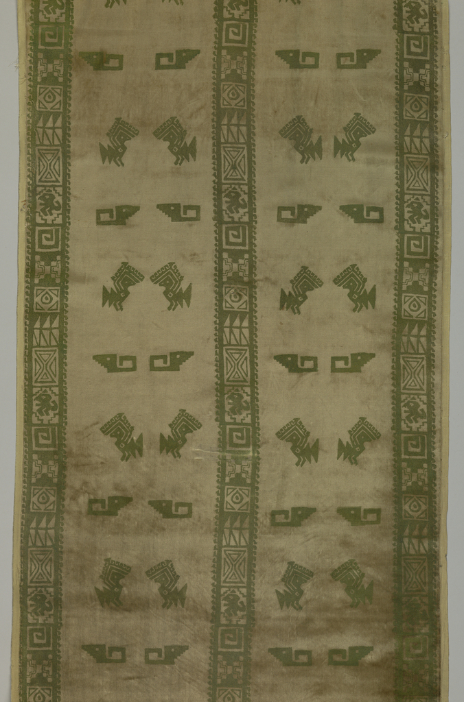 Two identical panels of printed velvet with pre-Columbian Peruvian motifs – a bird and a stepped fret – in two vertical columns bordered on two side, center and bottom edges by a narrow band comprised of six repeating geometrical motifs. Possibly used as a dress or tunic fabric.