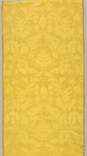 Bright yellow damask with a pattern of a symmetrical flower and leafy vine motif: central flower framed by flower sprigs with twisting leaves. The ogee pattern is continued by putting the fabrics side by side. Red stripe in either selvedge.