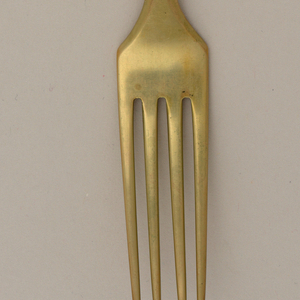 "Dessert fork of gold-colored metal, handle tapering to simple point, engraved with monogram ""HMA""."