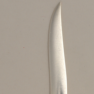Handle in the form of a gentle s-curve modeled to suggest leaves from which rises a sharp, pointed blade.