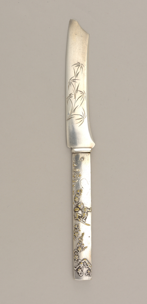 Knife in the form of a Japanese sword; handle with mottled surface, one side decorated with scene of a soldier in armor running; other side depicts bamboo trees, leaves, birds. Flat, curved blade engraved with stylized foliate decoration. Some guilding.
