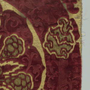 Gold brocaded red pile velvet in a pomegranate design. Orphrey of gold couched with multicolored silks show eight saints. Faces of saints are an applique of silk embroidery. Hood, in the same technique as orphrey, shows the Annunciation.