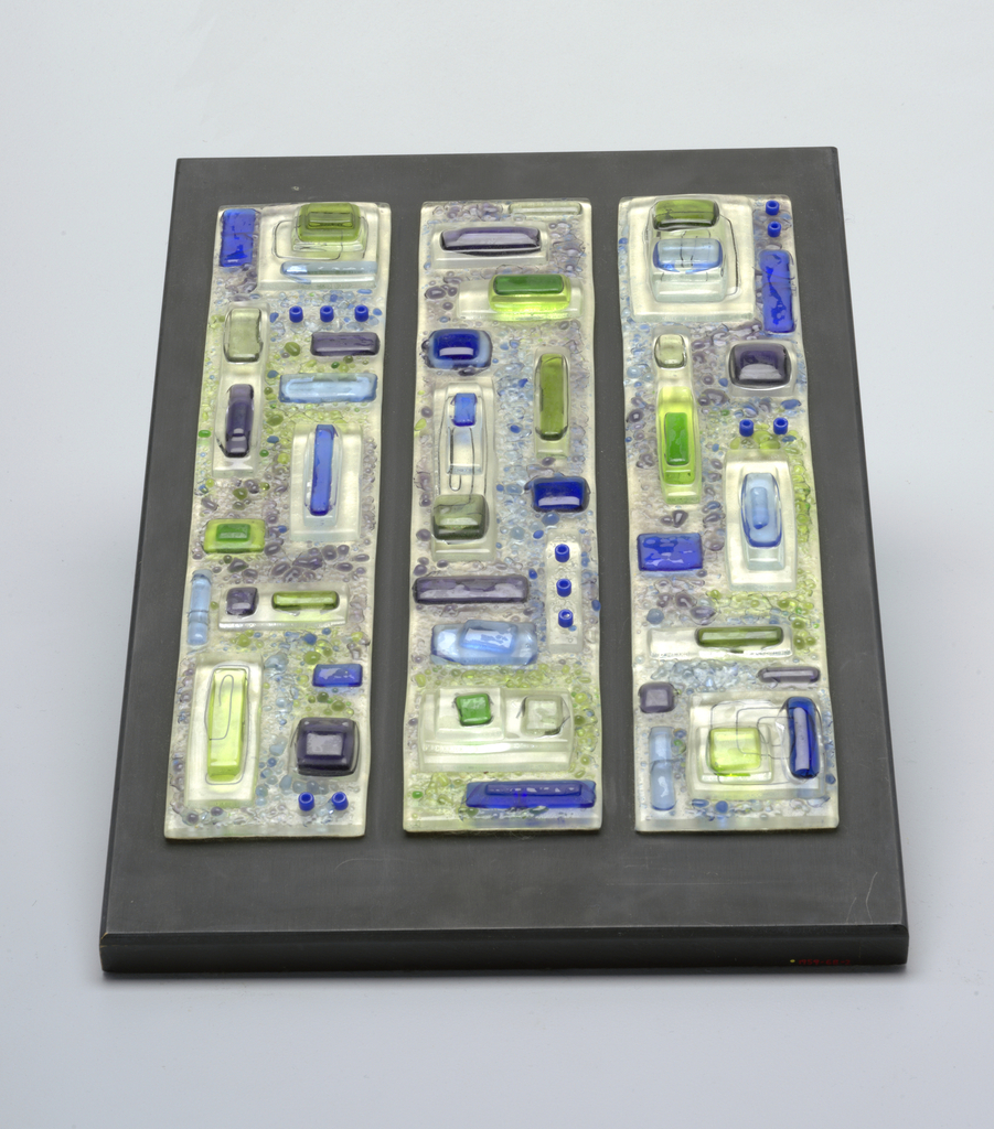 Three long rectangles of clear glass, with fused-on bits of blue, green and purple glass, occasionally reinforced by wire. Each panel backed with white felt and mounted together on rectangular wood plaque painted dull black