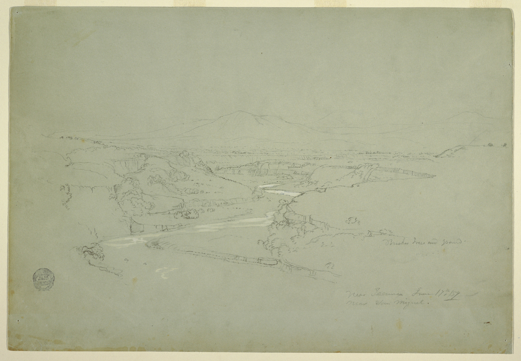 Horizontal view of a valley with a winding stream cutting into a plateau with mountains in the background.
