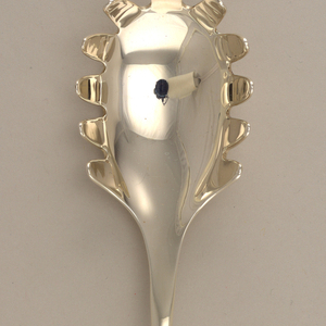 Silver pasta server with closed loop at end of handle.