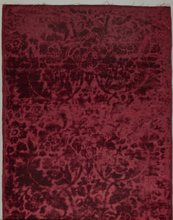 Rectangle of so-called frappe velvet in deep ruby with naturalistic design of flowers closely surrounded by plumelike leafage, rising slightly above pressed ground. Selvages appear to have been cutt off. Lined and edged with galloon.