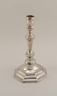 Eight-sided base from which rises a shaft with knobs and sockets of eight sides. Coat-of-arms engraved on the base.