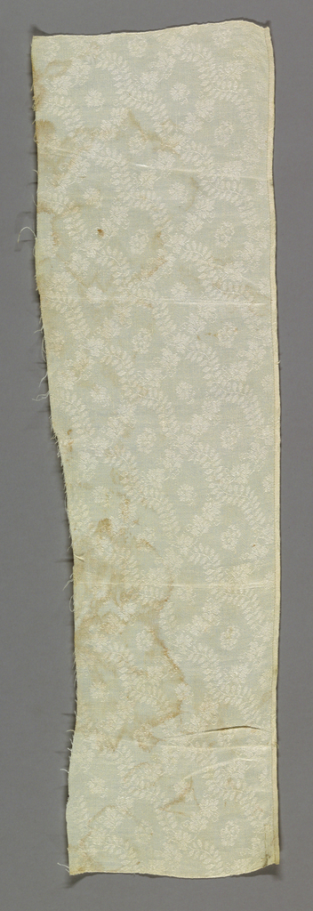 Fragment of a white damask napkin with a design of a fine diagonally running vine with tiny pointed leaves crossing a small grapevine running in the opposite direction. Small flower in center formed by crossing vines. Lower edge hemmed.