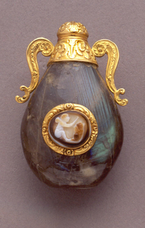 A carved stone bottle with a gold bordered cameo on the front. Decorative top in gold.