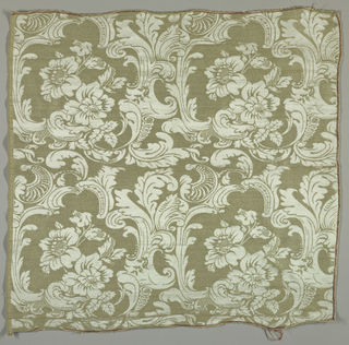 Sample of a large-scale flower enclosed in irregular frames of baroque acanthus leaves in light grey-green on a white satin ground.