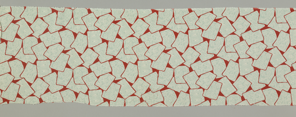 Bright red ground with scattered and overlapping rectangles in grey with white designs inspired by Aztec patterns.