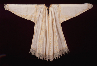 Shirt-like garment of white linen, with a full body gathered into a straight neck band, slit at front neck opening, and long sleeves narrowing to the wrist. Bobbin lace insertions at each seam are further embellished with floral embroidery in pale yellow silk, and bobbin lace trims the collar, sleeves and hem of the garment.