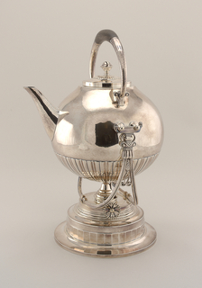 Silver round kettle on a heating stand. Kettle has vertical scalloped decoration on lower third of body. Tray and stand with round foot.