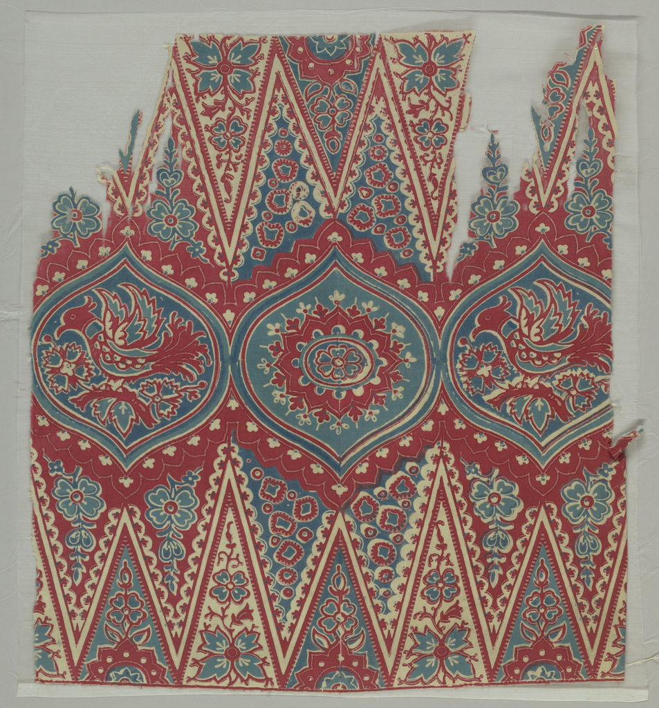 Row of three ogival medallions: middle one with rosette, outer two with crested bird and flowers as well as remnants of deep toothed zigzag border on either side. Much filling decoration. In reds and blues on very fine white cotton ground.