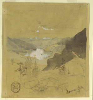 Vertical view of a lake surrounded by mountains, with snow capped ones in background and a few pines in the foreground.