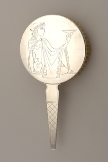 Circular, with tapering handle.  Back engraved with stylized, reclining ancient Greek female figure holding bowl and jar.  Handle engraved with cross-hatched decoration.