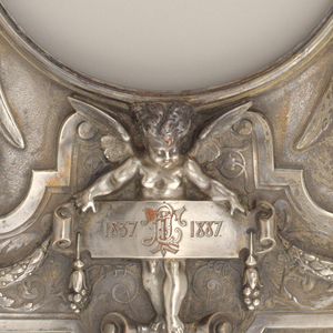 Rectangular form with two female figures supporting a circular opening on either side and surmounted by angels blowing horns, the opening supported by a plaque with the dates 1837- 1887--possibly commemorating Queen Victoria's Golden Jubilee--and the initials LJT(?).