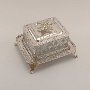Rectangular sardine box comprising rectangular cut glass box (a) imitating cut crystal; stepped lid (b) with stamped decoration and knop in form of two crossed sardines; rectangular tray (c) having gallery with japanesque decoration, and four scrolling feet at the corners.