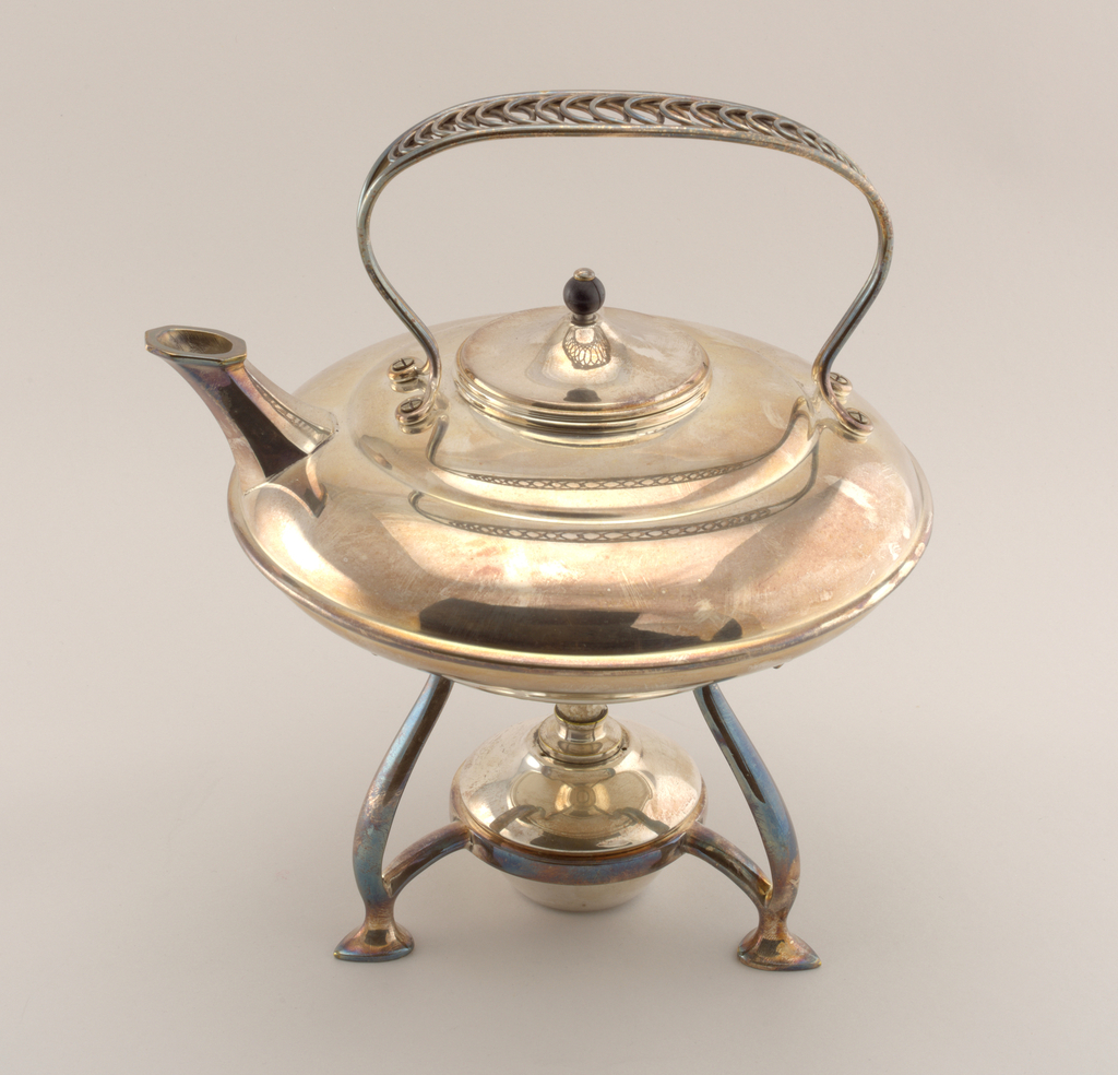 Squat circular teapot (a) having split strap handle with looped wire decoration through center, above a conical lid (b) with spherical ebonized wood knob. Teapot sits on circular tripod stand (c) with curved legs terminating in pad feet; circular burner (d) sits in base of stand.